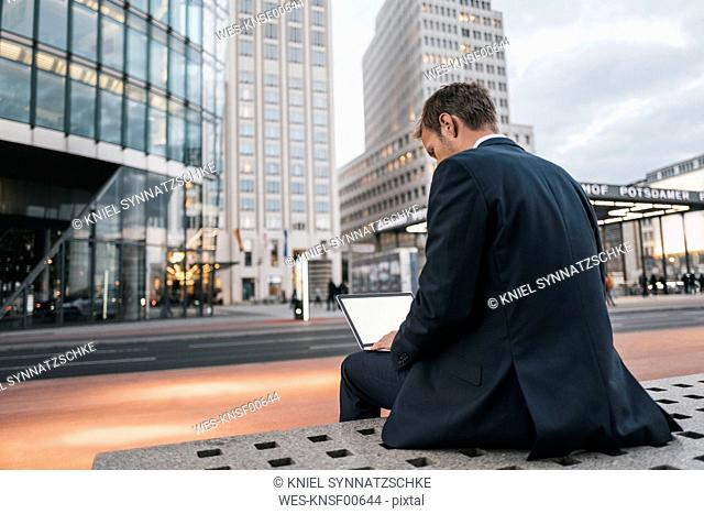 Germany, Berlin, Potsdamer Platz, Back view of businessman sitting on bench using laptop in the evening