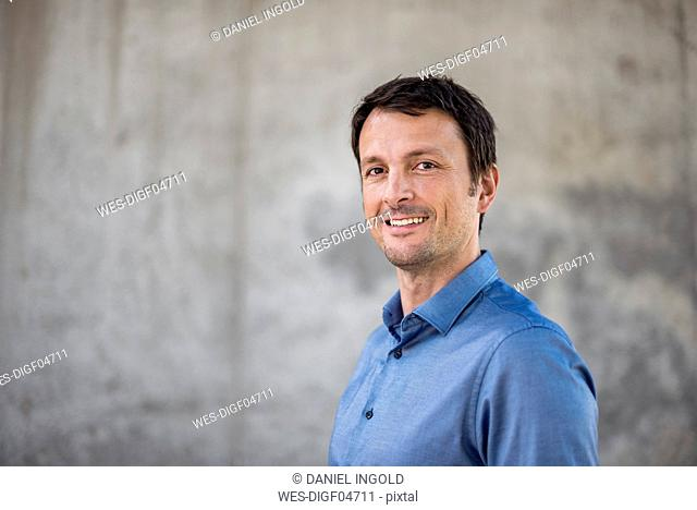 Portrait of smiling businessman in front of concrete wall