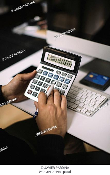 Man using calculator at desk, partial view