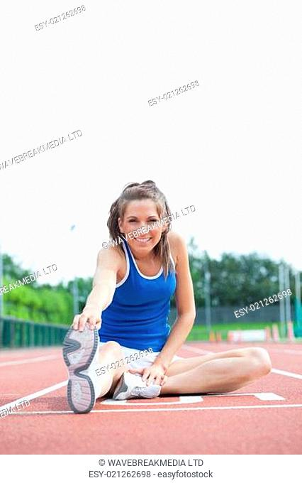 Woman stretching legs on running track