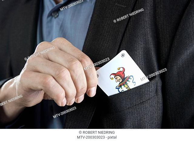 Man putting joker playing card on his pocket, Bavaria, Germany