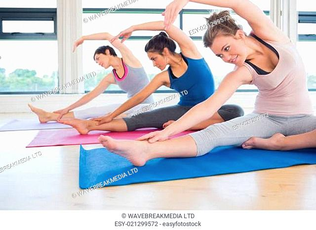 Women stretching on the floor in a gym