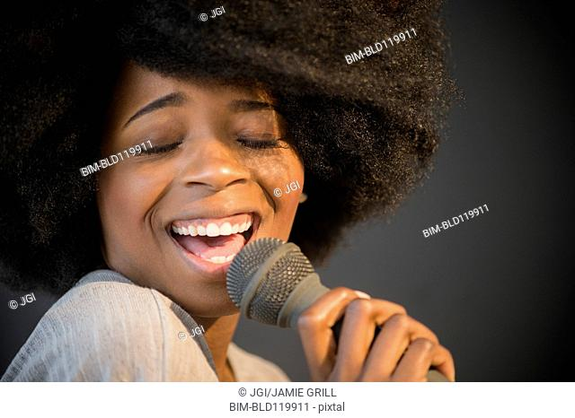 Mixed race woman singing into microphone