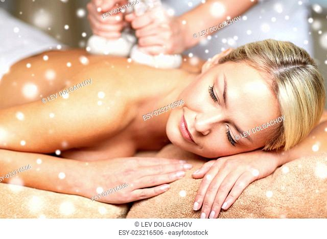 people, beauty, spa, winter and relaxation concept - close up of beautiful young woman lying and having herbal bag back massage in spa salon with snow effect