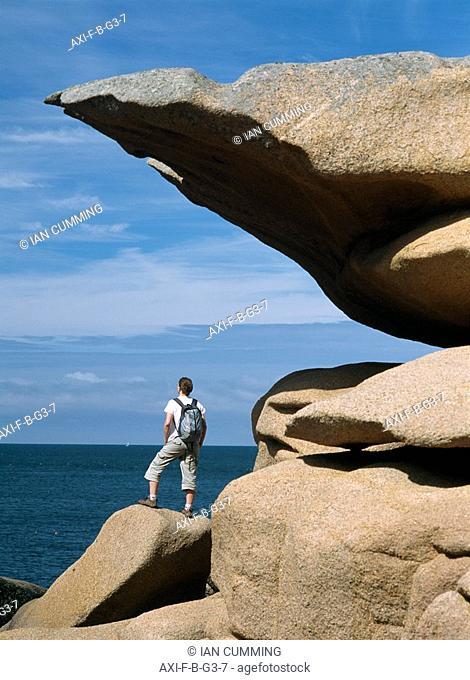 Woman walker standing beside rock formation by sea