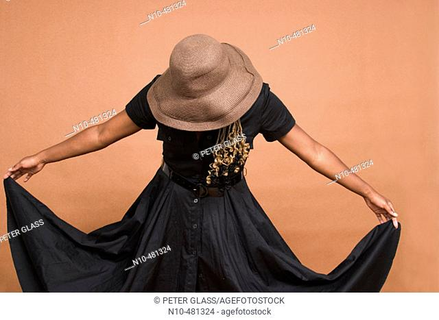 Young black woman, wearing a hat, holding up the corners of her dress