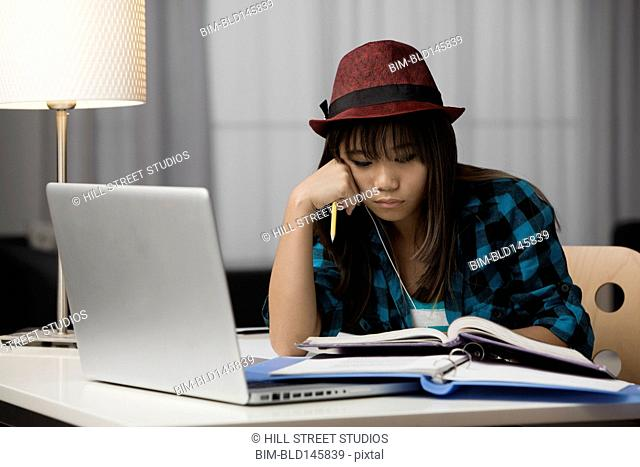 Chinese teenager studying at desk with laptop