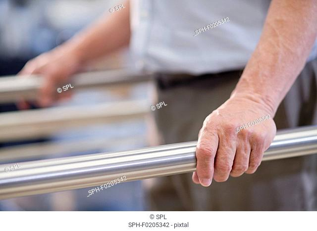 Man using parallel walking bars in hospital