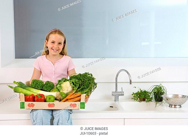 Girl 4-6 sitting on side in kitchen with box of vegetables on lap, smiling, portrait