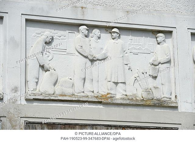 23 May 2019, Mecklenburg-Western Pomerania, Murchin: The artistically designed façade of the Kulturhaus Murchin shows agricultural figures