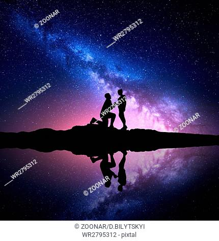 Milky Way. Night starry sky with silhouettes of a couple
