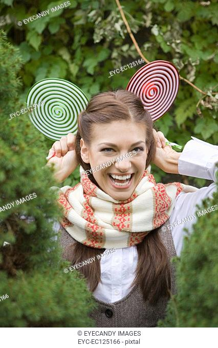 Portrait of young woman holding lollipops behind head in park
