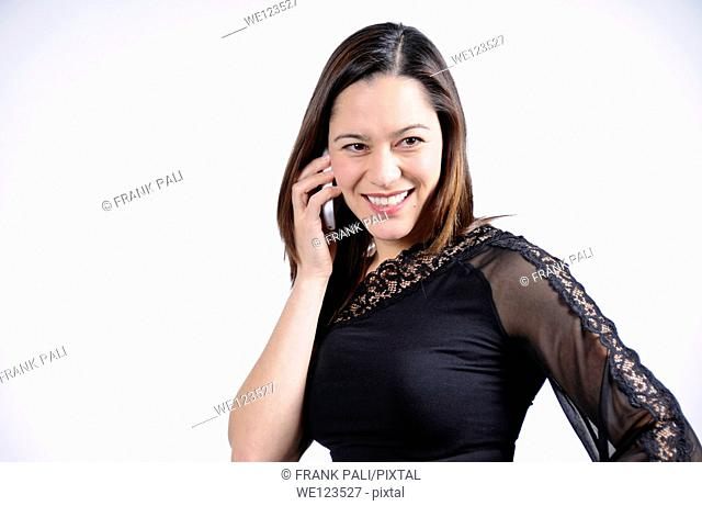 young woman talking on the telephone and is smiling  She is of mixed ethnicity
