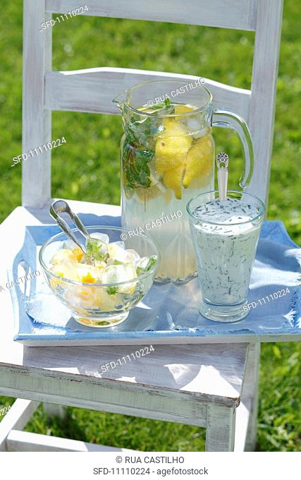 Lemonade, a cucumber and dill drink, ice cubes with orange zest and herbs