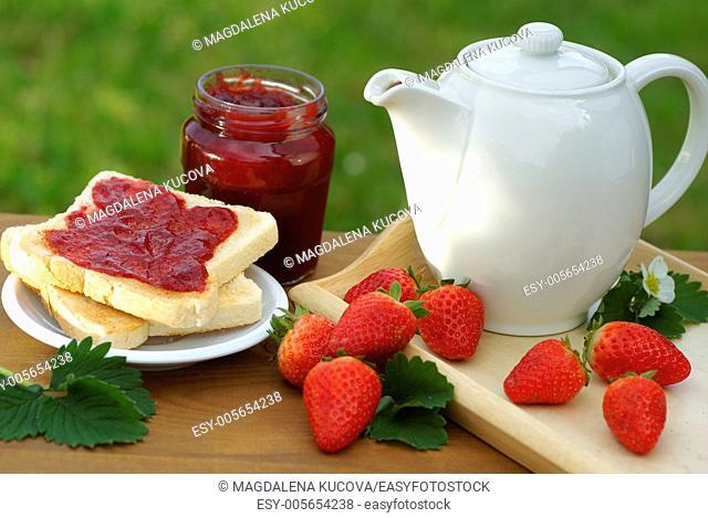 Mug, toast, glass with strawberry jam and strawberries