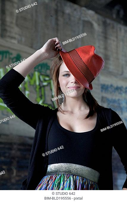 Smiling Caucasian teenage girl tipping hat on head