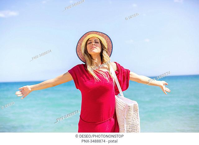 Happy blonde woman arriving at the beach