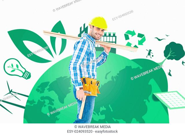 Composite image of smiling worker carrying wooden planks