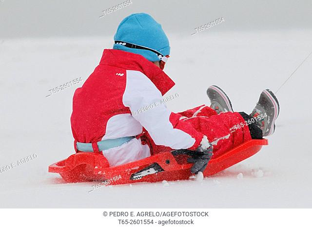 A child with his sleigh gliding enjoys his sleigh through the snow in O Cebreiro Lugo