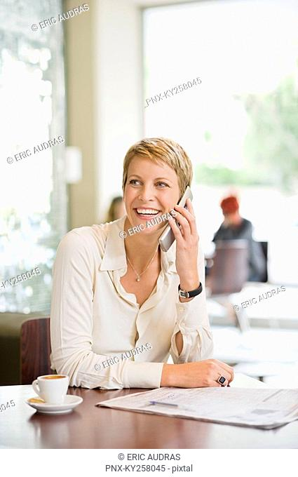 Businesswoman sitting in a restaurant and talking on a mobile phone