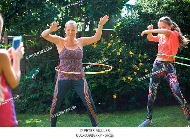 Girl photographing mother and teenage sister hoola hooping in garden