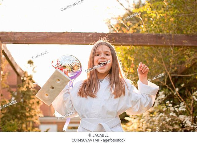 Portrait of girl celebrating trophy in garden