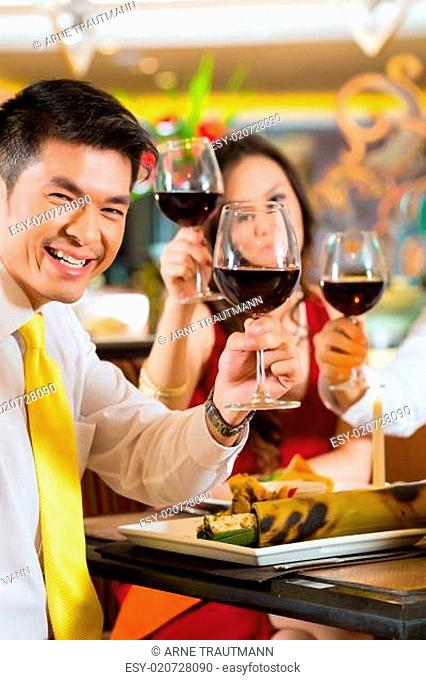 Chinese couples toasting with wine in restaurant