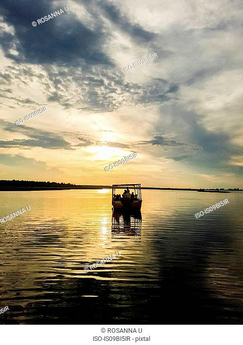 Silhouette of boat on river at sunset, Chobe National Park, Botswana