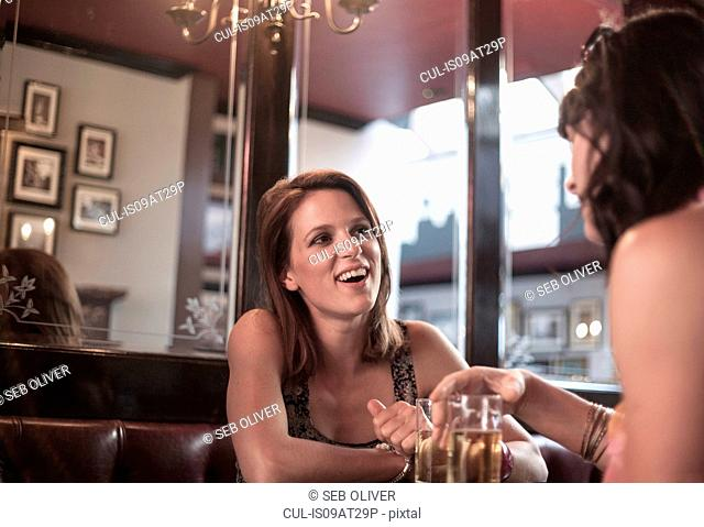 Two female adult friends drinking beer and gossiping in pub