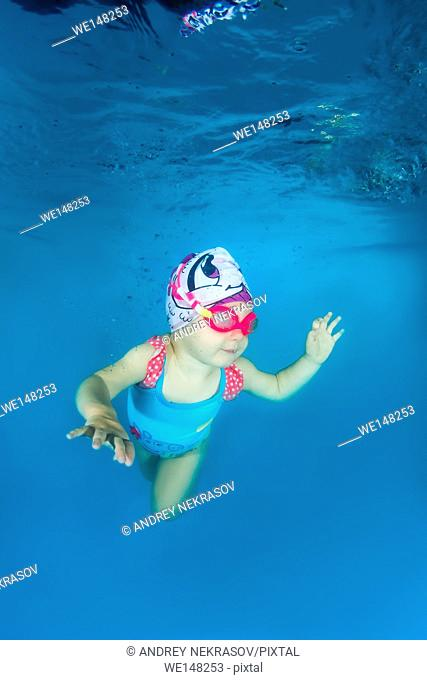 2 years girl in a swimming goggles learning to swim underwater in the pool, Odessa, Ukraine