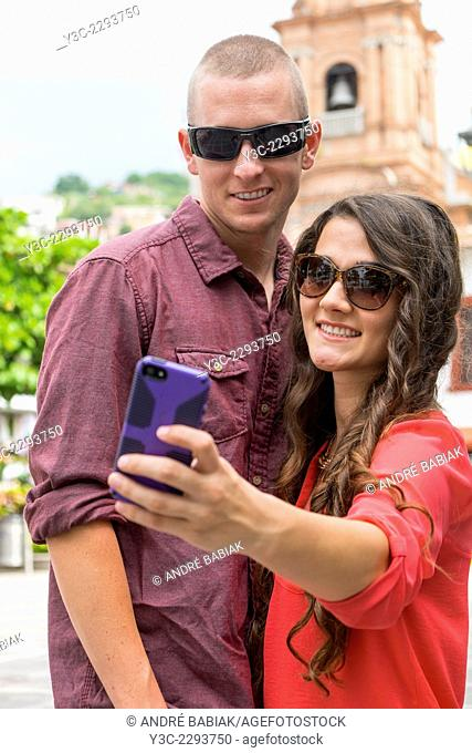 Young man and woman taking a picture of themselves with a smartphone camera in front of church of Our Lady of Guadalupe in Puerto Vallarta, Mexico