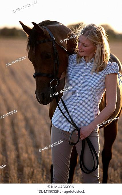 A young woman looking at an Arabian horse