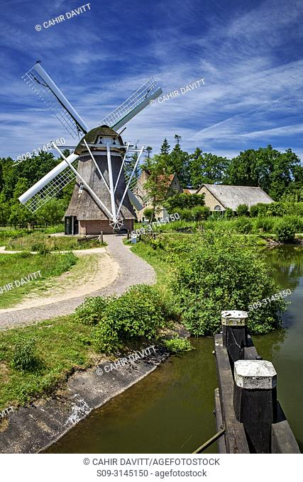 Traditional drainage windmill in the foreground and farmhouse in the background in the Netherlands Open Air Museum, Hoeferlaan, Arnhem, Gelderland, Netherlands