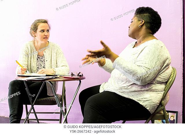 Newark, New Jersey, USA. LGBTQ Community Center volunteer Tyett giving an interview to a female journalist
