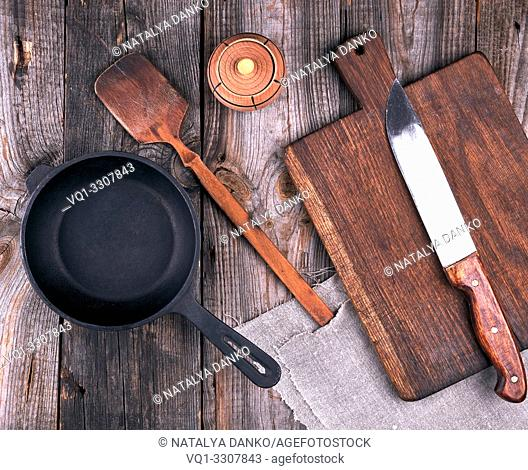 empty black round cast iron pan with handle, wooden cutting board and knife on a gray table, top view