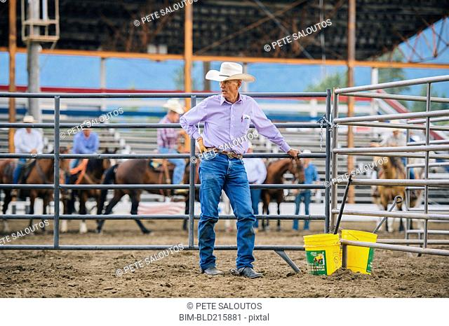 Caucasian cowboy standing at rodeo fence