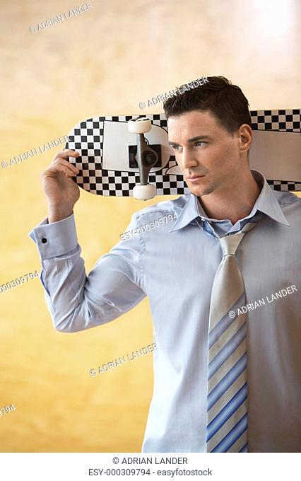 Man holding skateboard behind head portrait