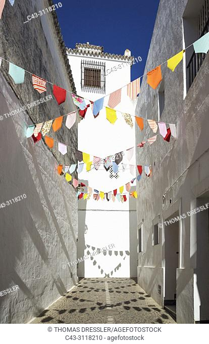 Alley and brilliantly whitewashed houses in the hilltop White Town of Arcos de la Frontera. The little colourful flags are remains of a feast that took place...