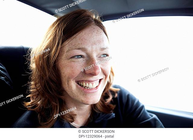 A Woman With Red Hair And Freckles Smiling While Riding In A Car; Alaska, United States Of America