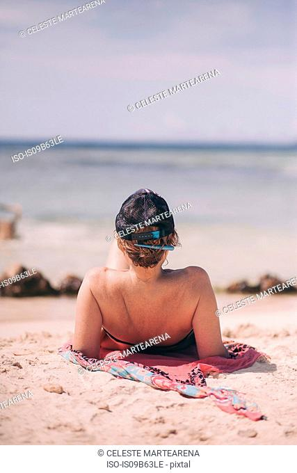 Rear view of woman reclining on beach looking out at sea, Angochi, Aruba, Lesser Antilles
