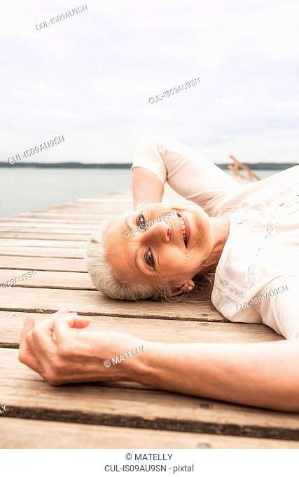 Senior woman relaxing on pier, smiling, elevated view