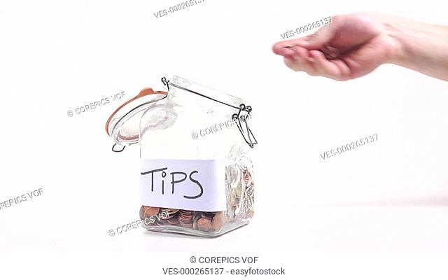 Person putting money in a jar for tips