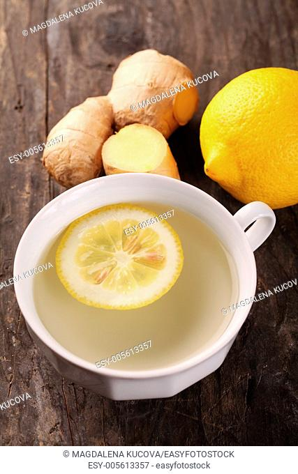 Cup of ginger tea and fresh ingredients - ginger and lemon