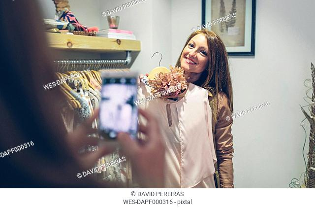 Woman taking picture of friend holding dress in a boutique