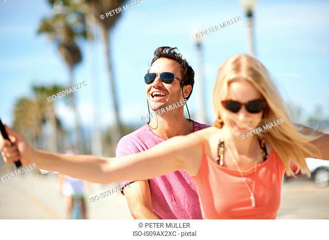 Couple outdoors, taking self portrait, using selfie stick