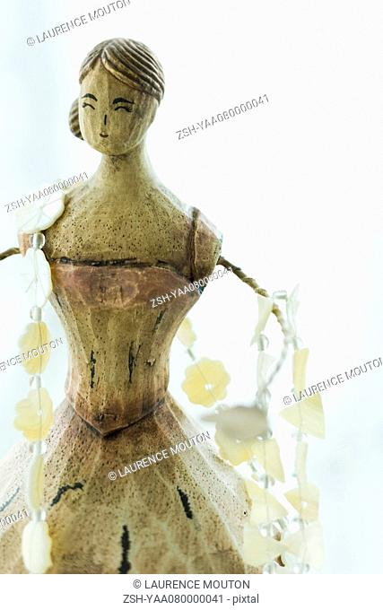Necklace draped across wooden necklace doll stand