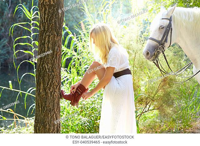 Blond woman fixing her boot with white horse in a romantic forest