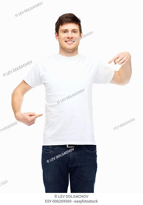 t-shirt design, gesture and people concept - smiling young man in blank white t-shirt pointing fingers on himself
