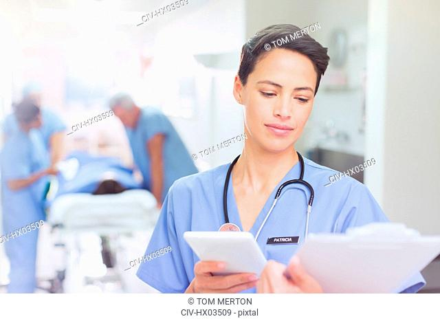Female surgeon with digital tablet reviewing clipboard paperwork in hospital corridor