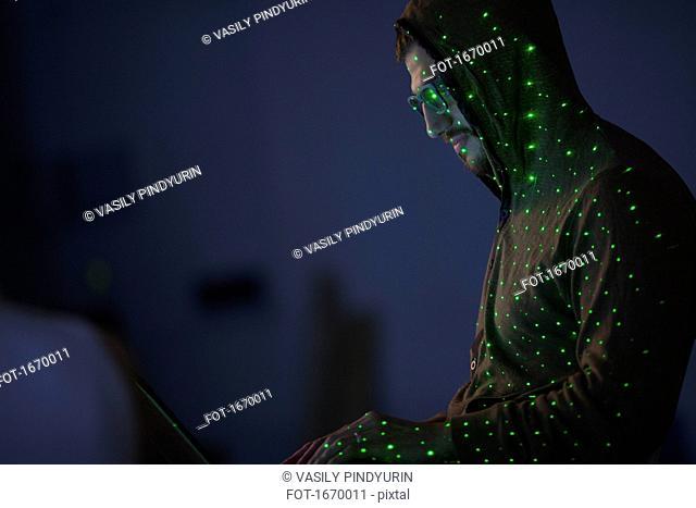 Green lights over computer hacker wearing hooded shirt using laptop